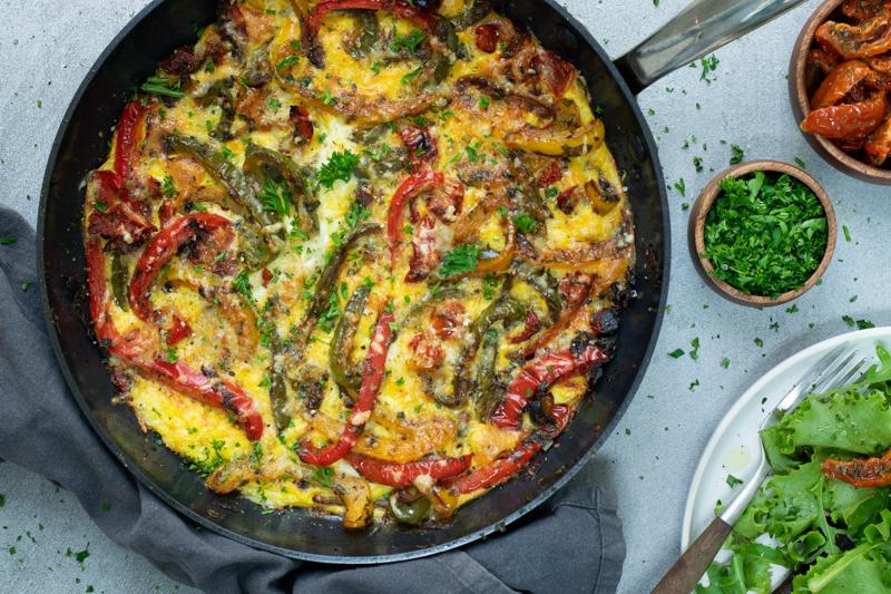 Een goudgele frittata met stukjes rode, gele en groene paprika, gepresenteerd in een pan, afgewerkt met wat gehakte peterselie.