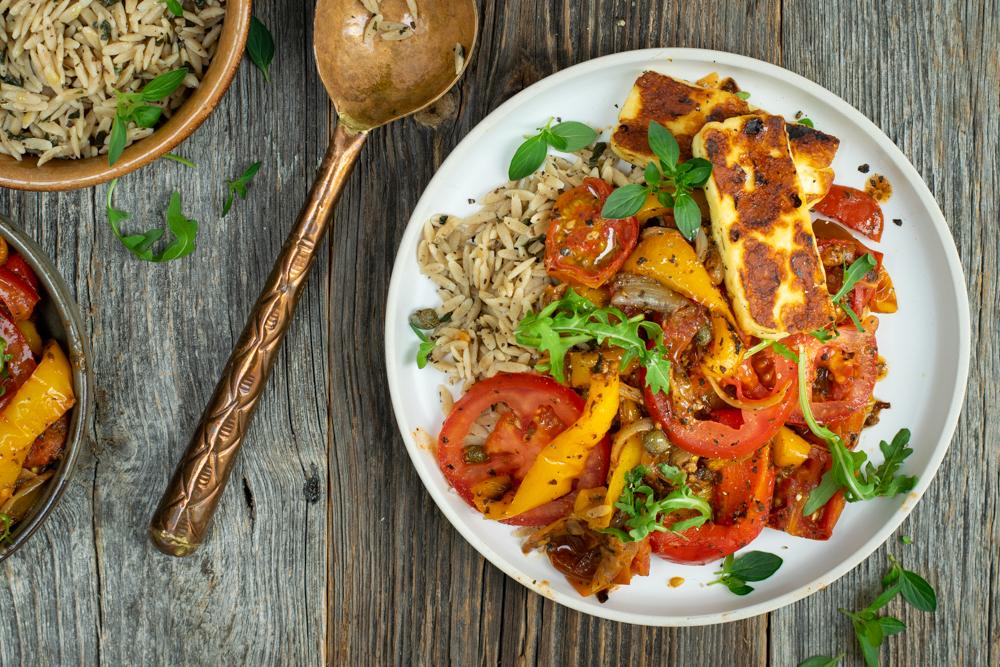 Bovenaanzicht van een gerecht, gepresenteerd op een wit bord. Het gerecht bestaat uit orzo, veel gegrilde, zachte tomaat en paprika, twee plakjes gebakken halloumi en enkele plukjes groene rucola en oregano.