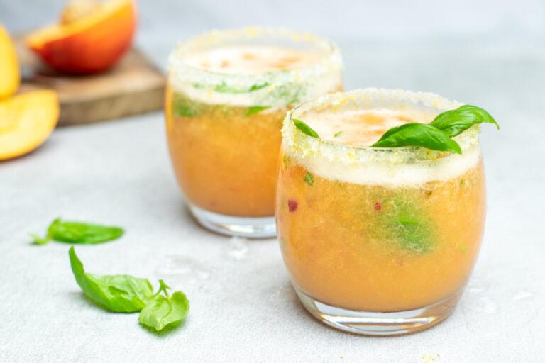 Fizzy nectarinemocktail. Twee lage, bolle glazen met een perzikkleurig, schuimend aperitief.